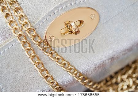 Close-up texture of evening silver small handbag from genuine leather with beautiful gold details. For background, backdrop, substrate, use of composition. Concept of shopping, manufacturing, lifestyle, holiday, weekend