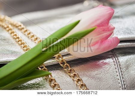 Close-up texture of evening silver handbag from genuine leather with beautiful gold details, decorated flower. For background, backdrop, substrate, use of composition. Concept of shopping, manufacturing, lifestyle, holiday, weekend