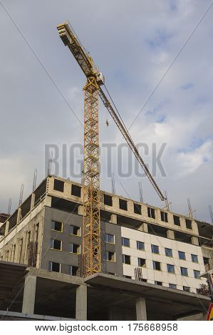 Building and Construction Concepts. Construction Building Site With Industrial Mid-Size Crane. Vertical Shot