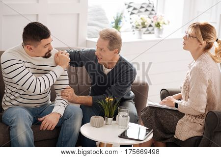 Relationship problems. Unhappy good looking gay couple sitting together on the sofa and having a quarrel while having a psychological session