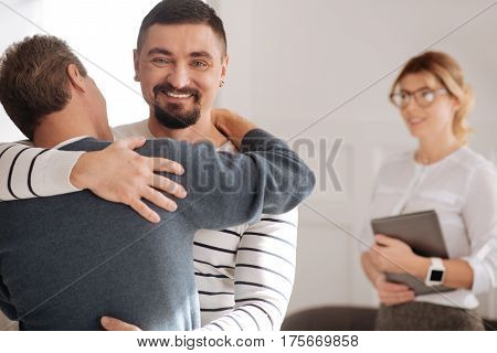 Happy couple. Joyful nice bearded man looking at you and smiling while hugging his boyfriend