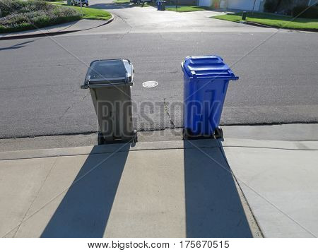 Two wheeled garbage containers (grey and blue) set out on street curbside on collection day, casting shadows on sidewalk.