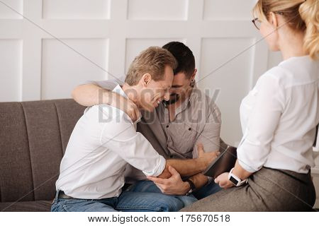 Sexual minority. Happy delighted gay couple sitting together and hugging each other while visiting a therapist