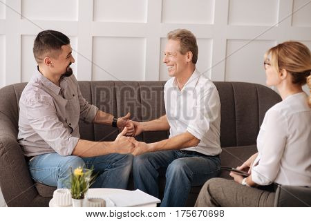 We are together. Nice joyful delighted gay couple holding their hands and looking at each other while sitting on the sofa