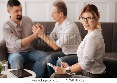 Professional psychologist. Joyful nice delighted woman sitting near her patients and smiling while helping them to find a solution of their problem