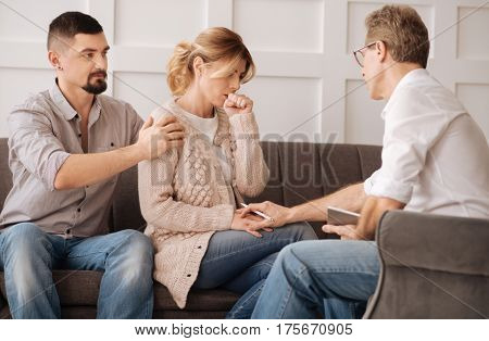 Be calm. Nice professional male psychologist holding a womans hand and trying to calm her down while having a psychological session