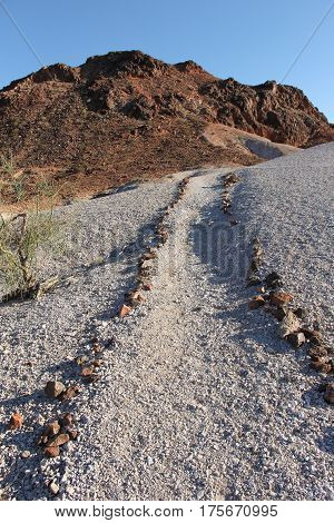 Path outlined with rocks up gravelly hill to granite outcrop in Picacho SRA, California, site of historic gold mining operation.