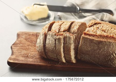 Wooden cutting board with sliced loaf of beer bread on table