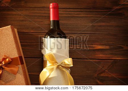 Decorated wine bottle and gift box on wooden background