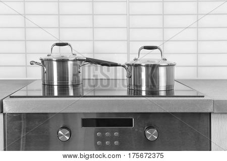 Two saucepans on electric stove in kitchen