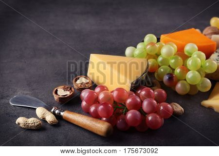 Sorts of cheese, grape and nuts on grey background