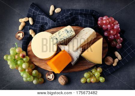Wooden board with variety of cheese on grey background