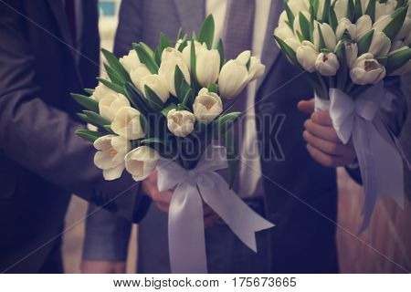 Groom and groomsman with beautiful bouquets