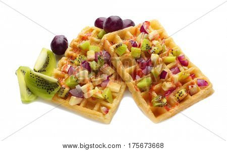 Tasty waffles with delicious fruits and syrup on white background