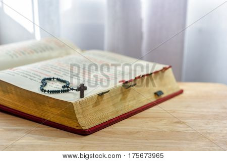 Catholic rosary beads and bible on wooden table