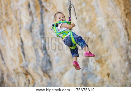 Little girl in climbing gear hanging on rope attached to safety harness