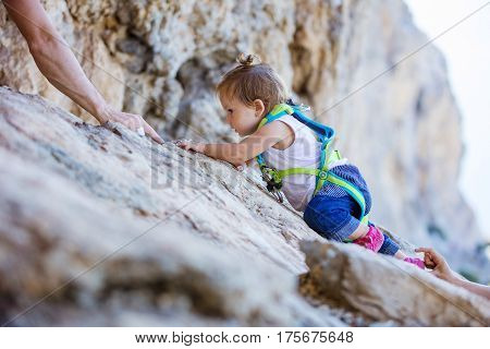 Little girl in safety harness climbing up cliff mom and dad safeguarding her from above and beneath