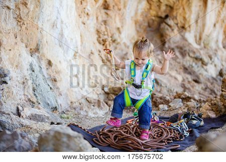 Happy little girl wearing safety harness and playing with rock climbing gear