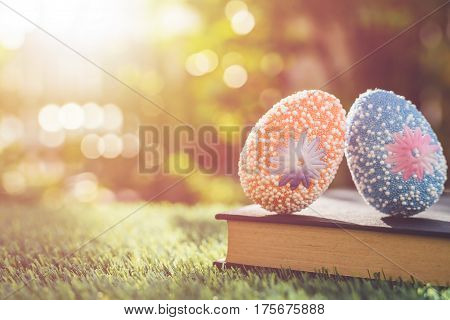 Color Eggs On Green Grass With Blur Bokeh And Sunlight Background. For Easter Day Use