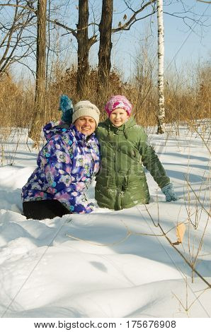 woman with a little girl playing in the winter forest