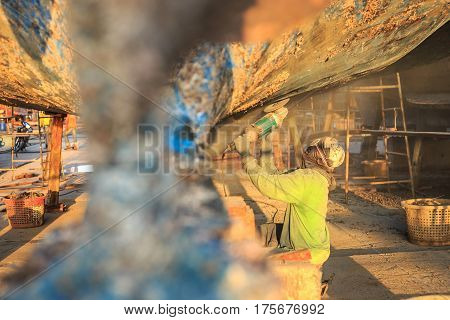 A Man Using Grinder In Preparation For Anti Foul Paint Being Applied
