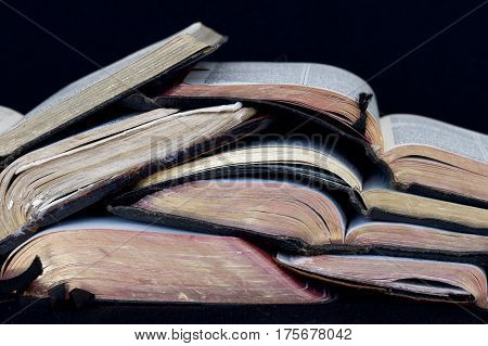 A stack of open old bibles and prayer books.