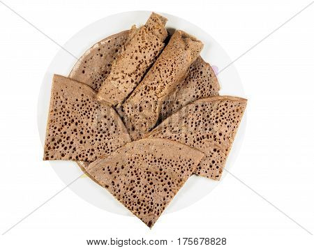 Traditional Ethiopian flatbread from fermented teff flour on a white plate cut and rolled up