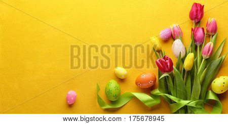 Easter eggs with tulip flower on fabric background