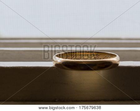 Anel de casamento antigo, em ouro, sob luz de fundo e gravações