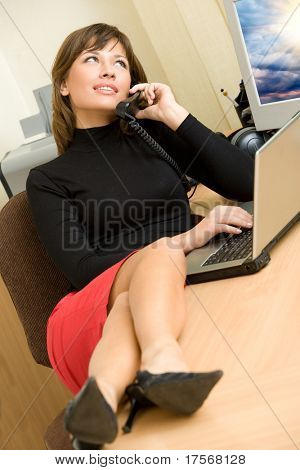 Beautiful girl talking on phone in office, legs over desk