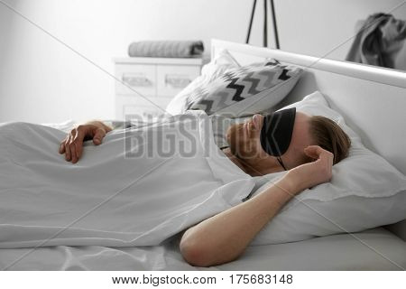 Handsome man sleeping with blindfold in bed at home