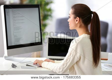 Young attractive programmer working at office