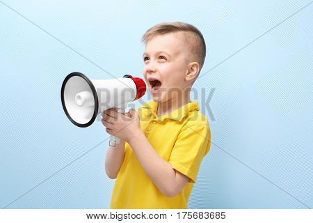 Cute little boy with megaphone on color background