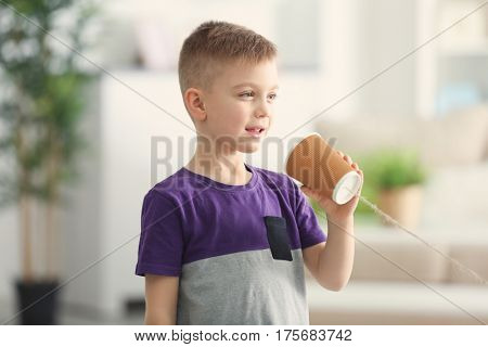 Cute little boy using plastic cup as telephone while playing at home