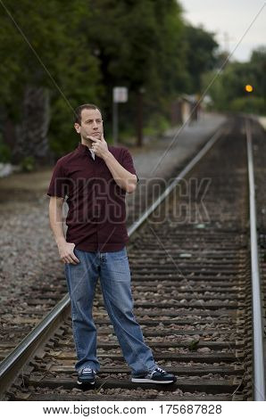 Man with hand on chin thinking of what tomorrow brings standing on train tracks.