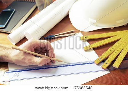 Hand drawing with pencil using ruler, construction plans with helmet, measure, mobile phone, and drawing tools