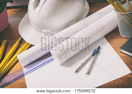 Construction plans with helmet and drawing tools on blueprints and measure
