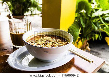 Sarawak Laksa in a white bowl in daytime