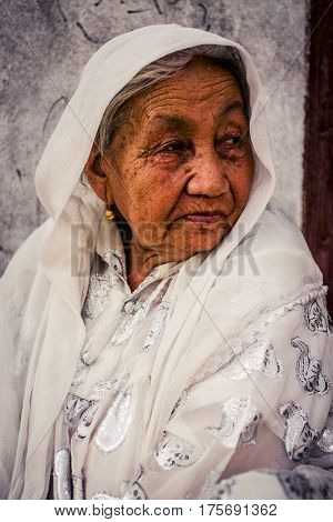 Kashgar China - 28 June 2009: Portrait ofa Uyghur woman at the Sunday Market a weekly marketplace that draws people from hundreds of kilometers in Kashgar