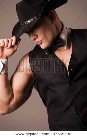 Attractive muscular male model wearing waistcoat and black hat