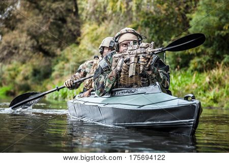 Special forces men with painted faces in camouflage uniforms paddling army kayak. Boat moving across the river, diversionary mission, front view