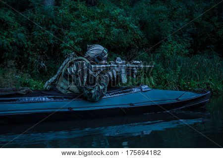 Special forces man with painted face in camouflage uniforms in army kayak. Seeking target, diversionary mission, twilight