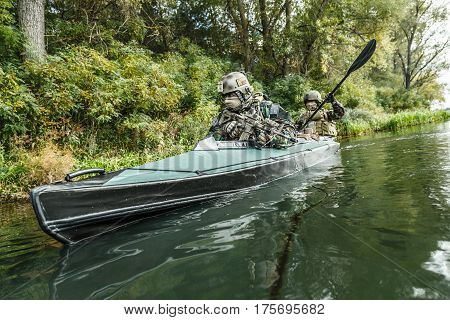 Special forces men with painted faces in camouflage uniforms paddling army kayak. Boat moving across the river, diversionary mission, diagonal view