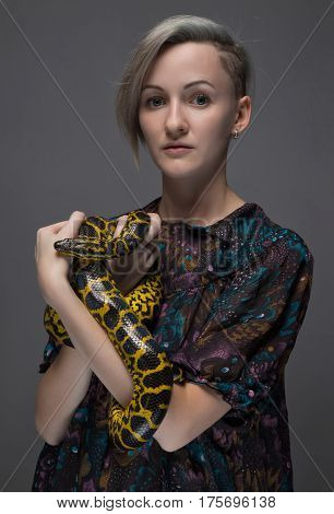 Young woman holding anaconda on gray background