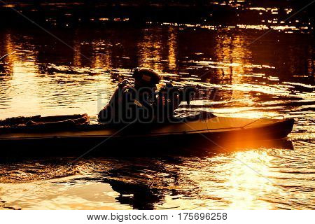Silhouette of special forces man with rifle in army kayak. Boat moving calmly across the river, diversionary mission, sunset dusk