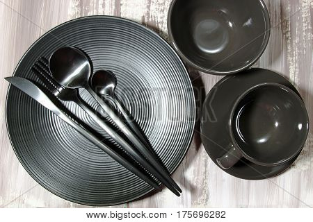 A still life of a black plate with spoon knife fork cutlery and a black tea cup and saucer on a wooden background selective focus.