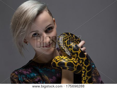 Blond smiling woman holding snake on gray background