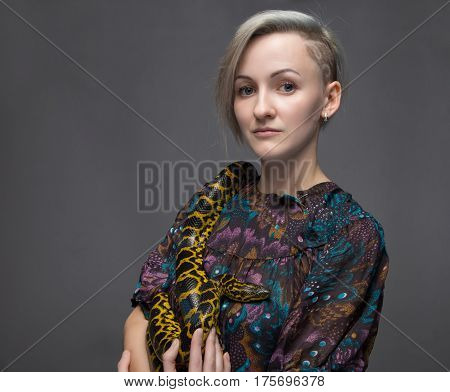 Young woman and yellow anaconda on gray background