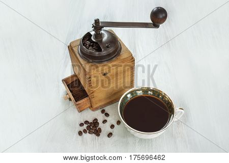 A photo of a vintage coffee grinder with a cup, coffee grains, and a place for text