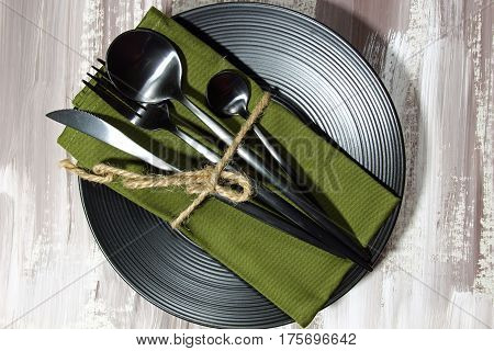 A black plate with fork spoon knife cutlery on a green napkin top view.